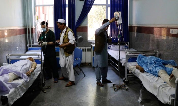 Afghan men receive treatment at a hospital after a bus was hit by a roadside bomb in Herat province, western Afghanistan on July 31, 2019. (Jalil Ahmad/Reuters)