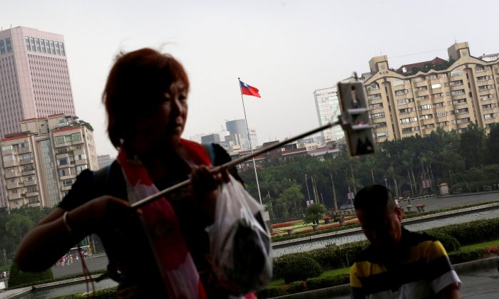 A tourist from China takes a selfie in front of a Taiwanese flag, in Taipei, Taiwan on May 5, 2016. (Tyrone Siu/Reuters)