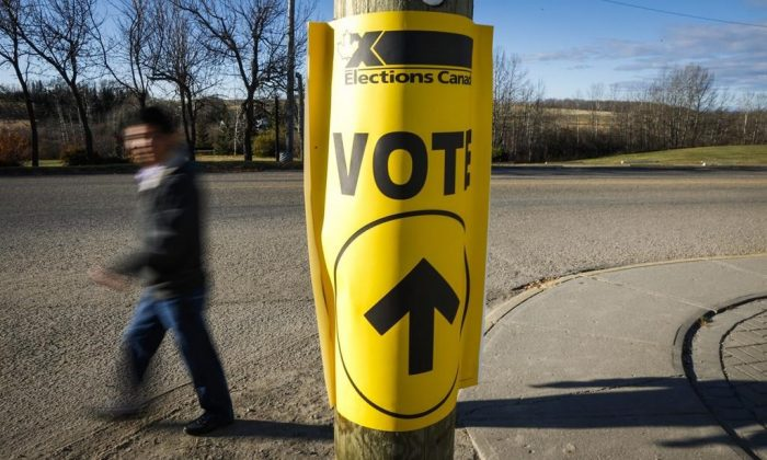 A voter walks past a sign directing voters to a polling station for the Canadian federal election in Cremona, AB., Oct. 19, 2015. (The Canadian Press/Jeff McIntosh)