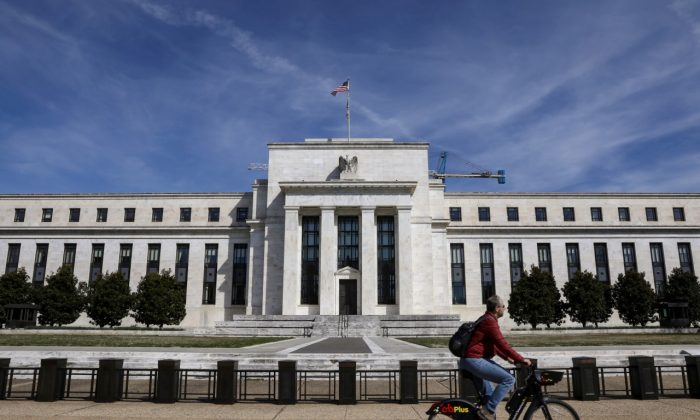 A man rides a bike in front of the Federal Reserve Board building on Constitution Avenue in Washington on March 27, 2019. (Brendan McDermid/Reuters)