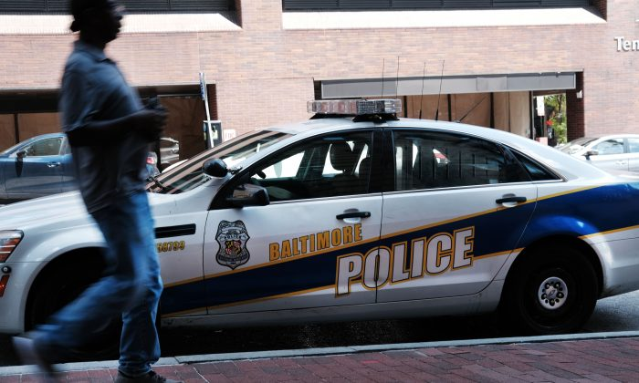 A person walks past a police car in Baltimore, Md., in a file photo.  (Spencer Platt/Getty Images)