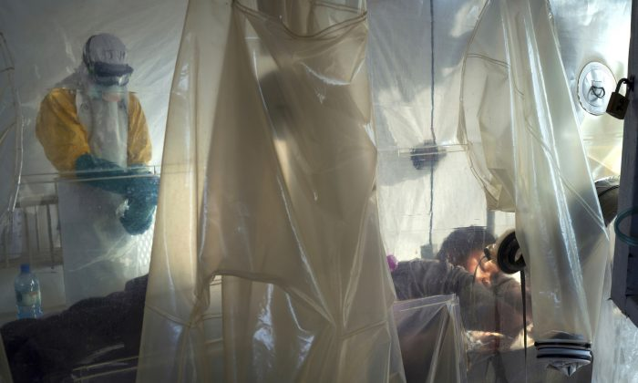 Health workers dressed in protective gear check on a patient isolated in a plastic cube at an Ebola  treatment center in Beni, Congo DRC onJuly 13, 2019. (AP Photo/Jerome Delay)