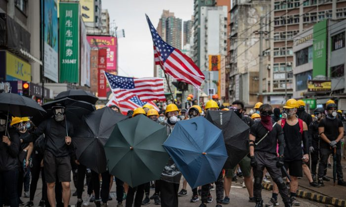Protesters hold up umbrellas and American flags in the face of advancing riot police in the district of Yuen Long in Hong Kong on July 27, 2019. (Laurel Chor/Getty Images)