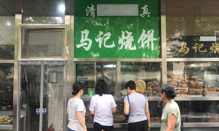 The Arabic script on the signboard of a halal food store is seen covered, at Niujie area in Beijing on July 19, 2019. (Reuters)