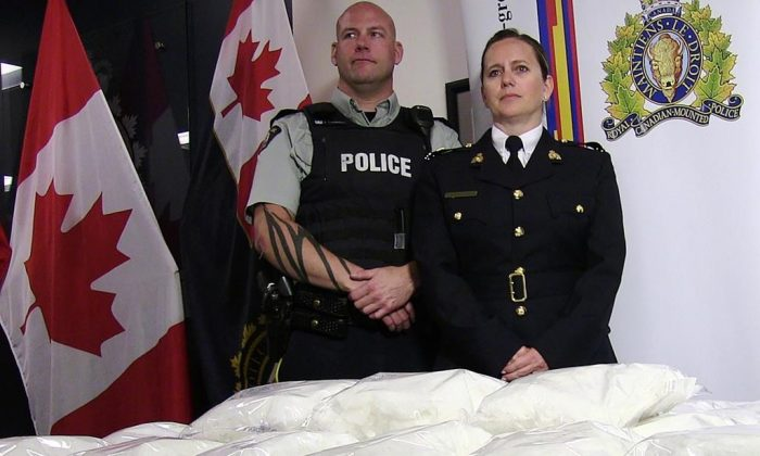 RCMP Cpl. Jon Cormier and RCMP Insp. Charlene O'Neill stand over seized methamphetamine from a truck at a Canada-U.S. border crossing in southern Alberta during a press conference in Calgary on August 1, 2019.  (Lauren Krugel/The Canadian Press)
