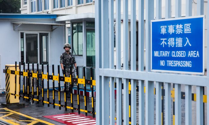 A Chinese People's Liberation Army (PLA) soldier guards the entrance to the PLA Forces Hong Kong Building, which is the headquarters for the PLA Hong Kong Garrison, in the Admiralty district in Hong Kong on August 1, 2019. (ISAAC LAWRENCE/AFP/Getty Images)