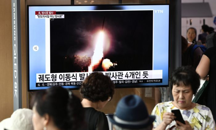 People watch a television news screen showing an image of North Korea's test-fire of a new multiple rocket launcher, at a railway station in Seoul on Aug. 1, 2019. (JUNG YEON-JE/AFP/Getty Images)