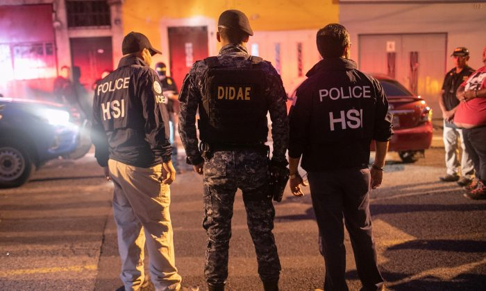 In this file image ICE agents with U.S. Homeland Security Investigations (HSI), and a Guatemalan policeman (C) stand at the scene of an early morning raid in Guatemala City on May 29, 2019. (John Moore/Getty Images)