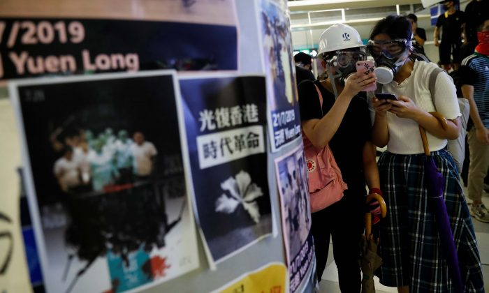 Protesters check their phones as they take part in a protest inside the Yuen Long MTR station, the scene of an attack by suspected triad gang members a month ago, in Yuen Long, New Territories, Hong Kong, China on Aug. 21, 2019. (Tyrone Siu/Reuters)