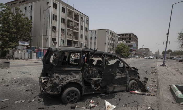 A destroyed vehicle remains at the site of a deadly attack on the Sheikh Othman police station in Aden, Yemen on Aug. 1, 2019. (AP Photo/Nariman El-Mofty)