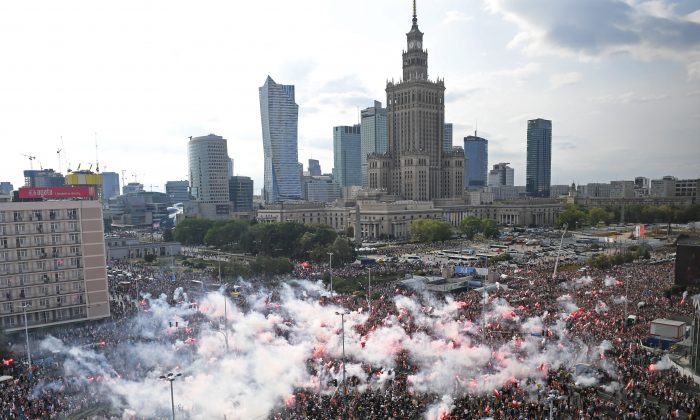 People light flares as they observe a minute of silence to mark the 75th anniversary of the Warsaw Uprising against Nazi German occupiers during World War II in Warsaw, Poland, on Aug. 1, 2019 (Janek Skarzynski/AFP/Getty Images)