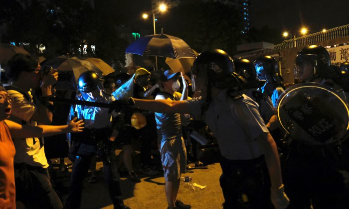 Police officers shout towards anti-extradition bill protesters who surrounded a police station where detained protesters are being held during clashes in Hong Kong, China on July 30, 2019. (Tyrone Siu/Reuters)