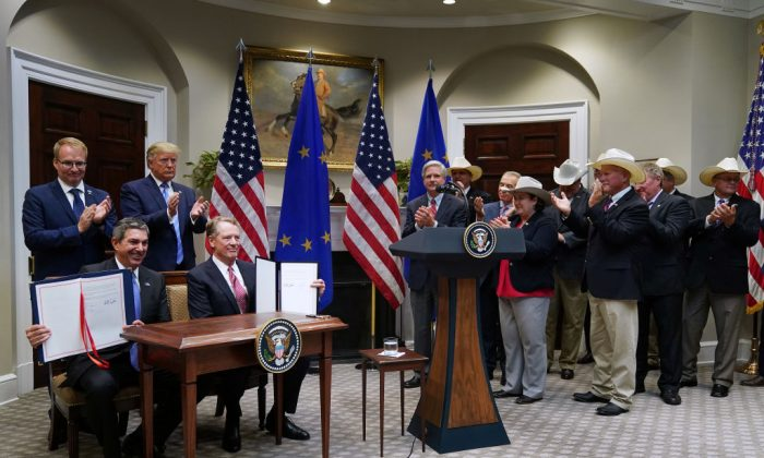 Deputy Head of Mission, for the Finnish presidency of the Council of the EU Jani Raappana, President Donald Trump, EU Ambassador to the United States Stavros Lambrinidis, (Seated L), and Trade Representative Robert Lighthizer (Seated R) are joined by representatives of the U.S. beef industry after signing a trade deal in the at the White House on Aug. 2, 2019. (Chip Somodevilla/Getty Images)