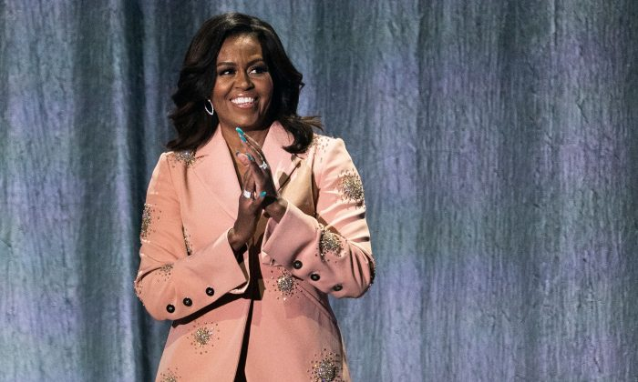 """Former US first lady Michelle Obama gestures on stage of the Royal Arena during a tour to promote her memoir """"Becoming"""" in Copenhagen, on April 9, 2019. (MARTIN SYLVEST/AFP/Getty Images)"""