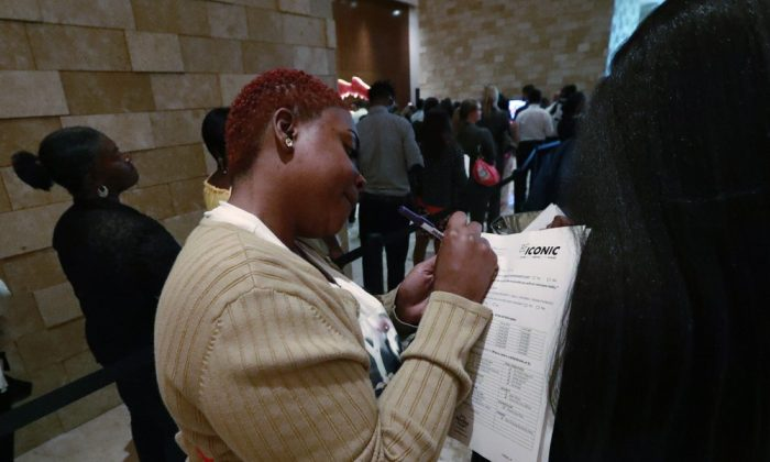 Job applicant Esta Williams (C), uses Tracy Simeton's back to fill out a questionnaire as they wait in line at the Seminole Hard Rock Hotel & Casino Hollywood during a job fair in Hollywood, Fla., on June 4, 2019. (Wilfredo Lee/File Photo via AP)