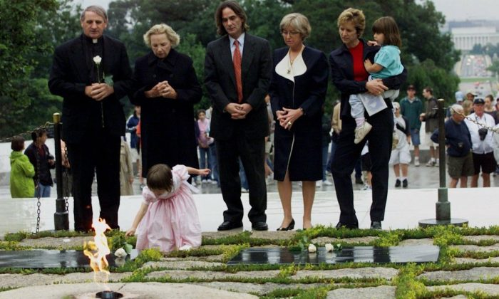 Robert F. Kennedy's granddaughter Saoirse Kennedy Hill places a white rose at the Eternal Flame, President John F. Kennedy's gravesite, at Arlington National Cemetery in Arlington, Va., on June 6, 2000. (Hillery Smith Garrison/AP Photo)