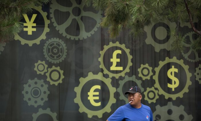 A deliveryman for American-based pizza chain Domino's prepares to make a delivery near a mural displaying Chinese yuan and other world currency symbols on the outside of a bank in Beijing on July 30, 2018. China's yuan fell on Aug. 2, 2019, to its lowest level of the year against the dollar following U.S. President Donald Trump's threat of new tariffs on Chinese goods, coming close to breaking the politically sensitive level of seven to the U.S. currency. (Mark Schiefelbein/AP)