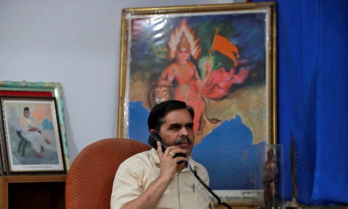 Ashwani Mahajan, chief of the Hindu nationalist Rashtriya Swayamsevak Sangh's (RSS) economic group Swadeshi Jagran Manch (SJM), poses for a photograph as he holds a phone inside his office in New Delhi, India on Oct. 31, 2018. (Altaf Hussain/Reuters)