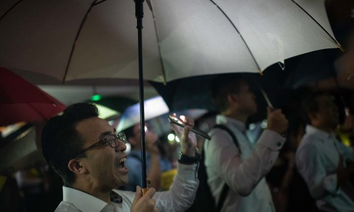 People from the finance community hold up umbrellas and shine lights during a rally against a controversial extradition bill in Hong Kong on Aug. 1, 2019. (Billy H.C. Kwok/Getty Images)