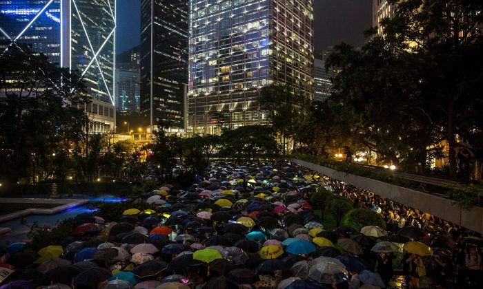People from the finance community hold up umbrellas and shine lights during a protest against a controversial extradition bill in Hong Kong on August 1, 2019. (Isaac Lawrence/AFP/Getty Images)