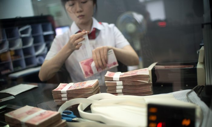 A worker of an Industrial and Commercial Bank of China Ltd (ICBC) branch counts money as she serves a customer in the China (Shanghai) Pilot Free Trade zone during a media trip on  Sept. 24, 2014. (Johannes Eisele/AFP/Getty Images)