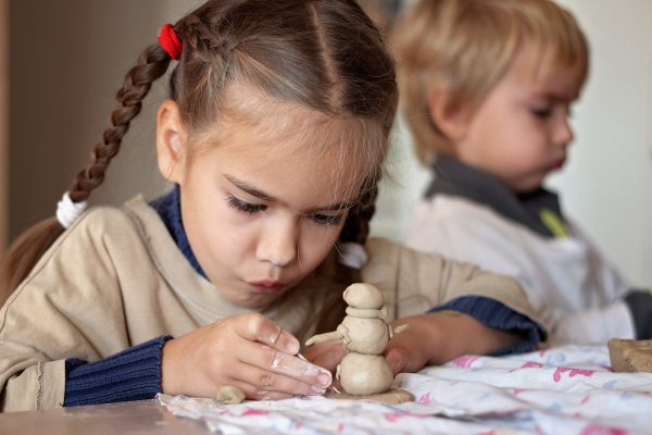 girl is playing with modeling clay in pottery workshop