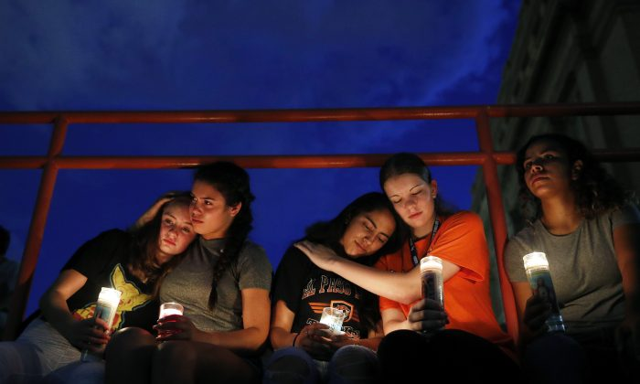 People comfort each other during a vigil for victims of the mass shooting in El Paso, Texas, on Aug. 3, 2019. (AP Photo/John Locher)