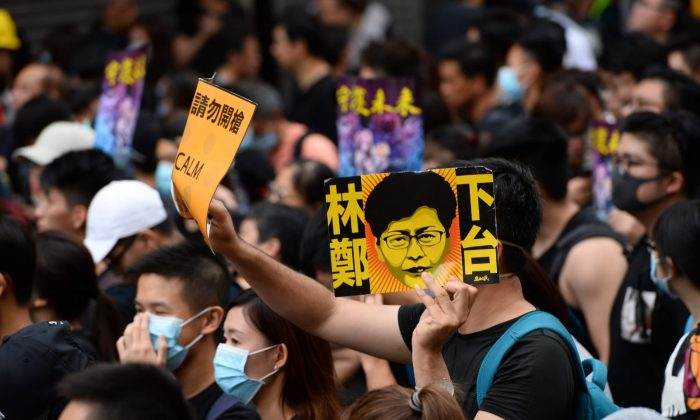 "One protester holds up a sign that says ""Carrie Lam Step Down"" in a march in Mong Kok, Hong Kong, on Aug. 3, 2019. (Song Bilong/The Epoch Times)"