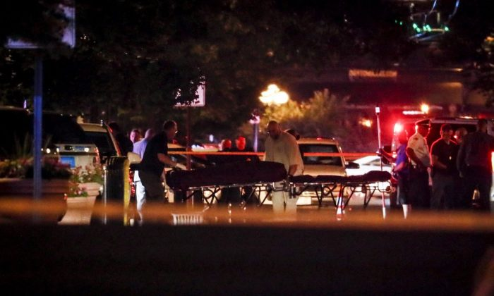 Bodies are removed from the scene of a mass shooting, Sunday, Aug. 4, 2019, in Dayton, Ohio. Several people in Ohio have been killed in the second mass shooting in the U.S. in less than 24 hours, and the suspected shooter is also deceased, police said. (AP Photo/John Minchillo)