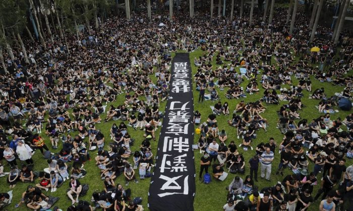 "People gather at Belcher Bay Park as they take part in an anti-extradition bill protest in Western district in Hong Kong, Sunday, on Aug. 4, 2019. The banner reads ""Against institutional violence, we want real elections."" (AP Photo/Kin Cheung)"