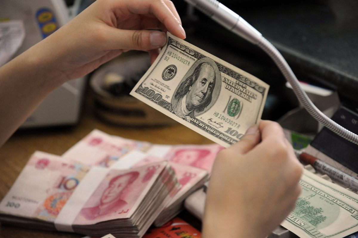 A Chinese bank worker checks a US 100-do