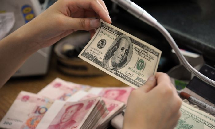 A Chinese bank worker checks a U.S. 100 dollar bill together with stacks of 100 yuan notes at a bank counter in Hefei City, Anhui Province, China, on Sept. 30, 2010. (STR/AFP/Getty Images)