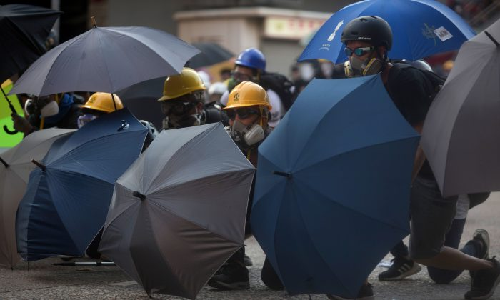 Protesters take shelter behind umbrellas after police fired tear gas in Wong Tai Sin during a general strike in Hong Kong on Aug. 5, 2019. (Isaac Lawrence/AFP/Getty Images)