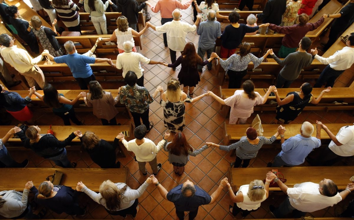 Churchgoers hold hands as they sing