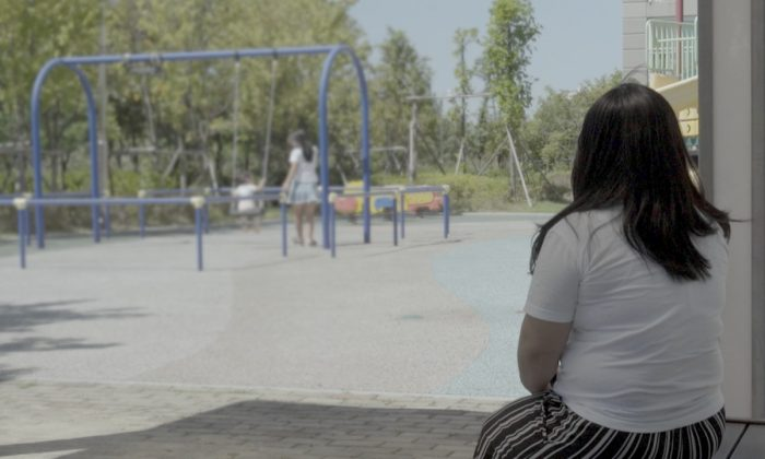 """""""Yoon Su Ryun,"""" a woman who was sexually assaulted while detained in North Korea for smuggling and who later fled North Korea, pictured watching her daughter and niece on a playground in South Korea, on Aug. 28, 2018. (©Human Rights Watch)"""