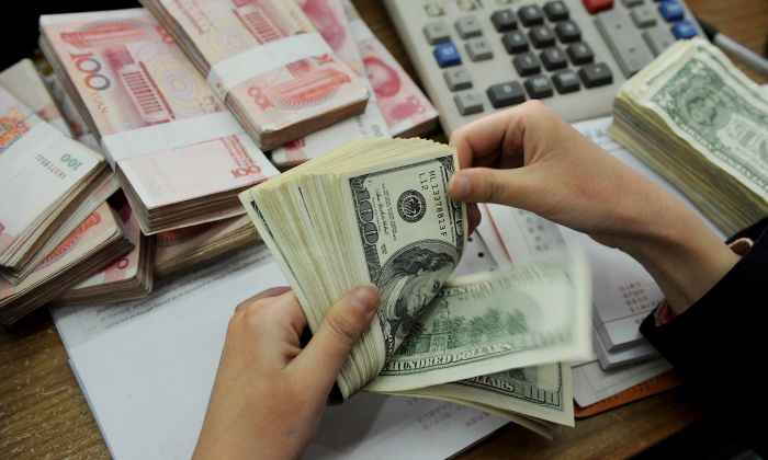 A bank teller counting stacks of US dollars and Chinese 100-yuan notes at a bank in Hefei, east China's Anhui province on Jan. 16, 2011. (STR/AFP/Getty Images)