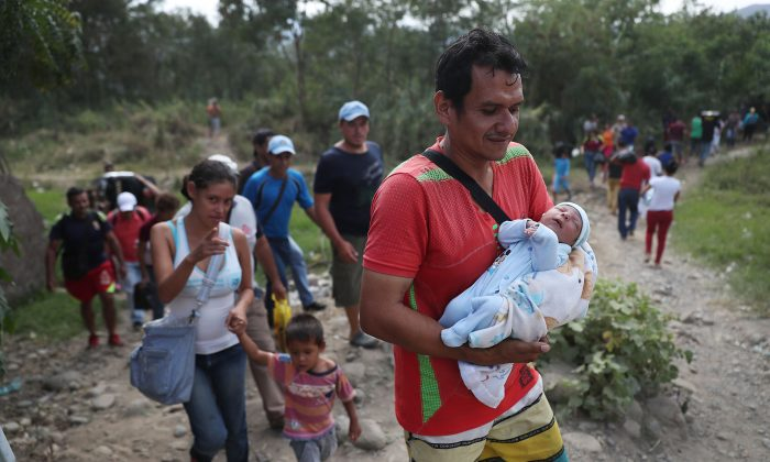 Javier Pinzon holds his 21-day-old baby, Jhosmar Pinzon, as he walks along a trail next to the Simón Bolívar international bridge, which connects Cúcuta with the Venezuelan town of San Antonio del Táchira after the closure of the border bridge on Mar. 1, 2019 in Cucuta, Colombia. (Joe Raedle/Getty Images)