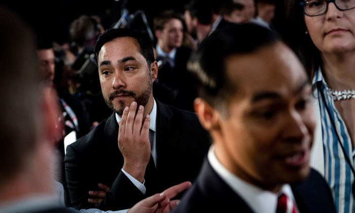 Joaquin Castro (L) listens to his brother Julian Castro (R) speak to reporters in the spin room after the second round of the second Democratic primary debate of the 2020 presidential campaign season hosted by CNN at the Fox Theatre in Detroit, Michigan on July 31, 2019. (Brendan Smialowski/AFP/Getty Images)