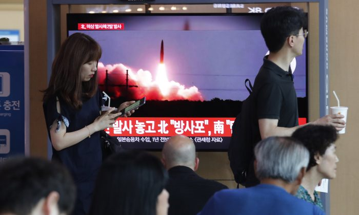 People watch a TV showing a file image of North Korea's missile launch during a news program at the Seoul Railway Station in Seoul, South Korea, Aug. 6, 2019. (AP Photo/Ahn Young-joon)