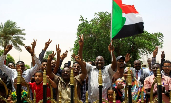 Sudanese people carry their national flag and chant slogans as they celebrate the signing of a constitutional declaration between Deputy Head of Sudanese Transitional Military Council, Mohamed Hamdan Dagalo and Sudan's opposition alliance coalition's leader Ahmad al-Rabiah, outside the Friendship Hall, in Khartoum, Sudan Aug. 4, 2019. (Mohamed Nureldin Abdallah/Reuters)