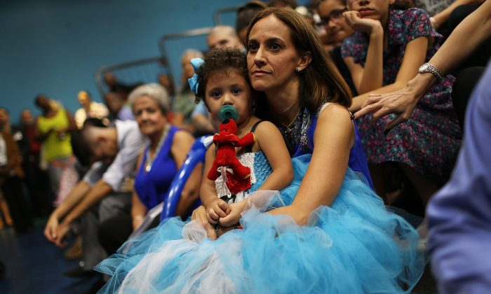Grace Gonzalez sits with her adopted daughter Bella Gonzalez, 2, during an adoption ceremony on National Adoption Day in Miami, on Nov. 20, 2015.  (Joe Raedle/Getty Images)