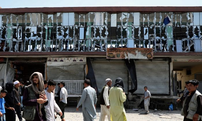 People walk in front of a building with broken windows at the site of a car bomb blast in Kabul, Afghanistan on Aug. 7, 2019. (Omar Sobhani/Reuters)
