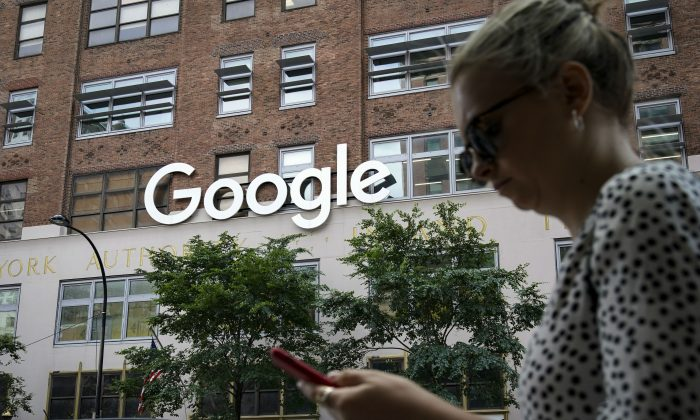 A woman looks at her smartphone as she walks past Google Building 8510 at 85 10th Ave. in New York City on June 3, 2019.  (Drew Angerer/Getty Images)