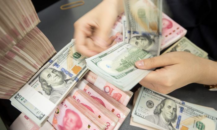 A Chinese bank employee counts 100-yuan notes and US dollar bills at a bank counter in Nantong in China's eastern Jiangsu province on August 6, 2019. (STR/AFP/Getty Images)