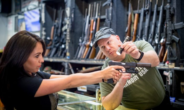 Edward Wilks, owner of Tradesmen Gun Store and Pawnshop helps a customer with a firearm at his store in Rifle, Colorado, on April 24, 2018. (Emily Kask/AFP/Getty Images)