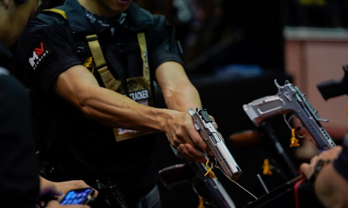 An attendee handles a semiautomatic handgun during the annual National Rifle Association's annual meeting in an April 2019 file photograph. (Bryan Woolston/Reuters)