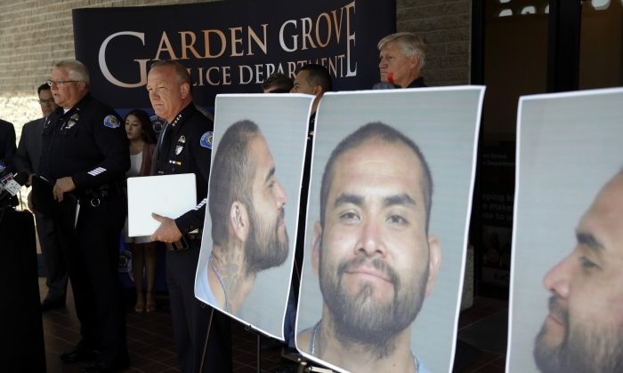 Garden Grove Police Chief Tom DaRe, center, and PIO Carl Whitney address the media next to a booking mug shot of Zachary Castaneda posted outside of the Garden Grove Police Department headquarters in Garden Grove, Calif., on Aug. 8, 2019. (AP Photo/Marcio Jose Sanchez)