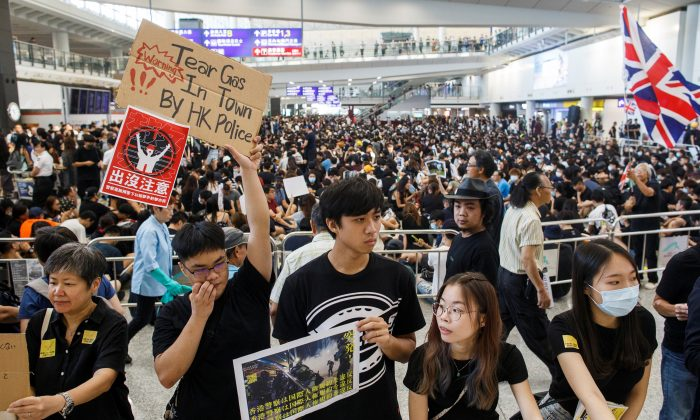 Anti-extradition bill protesters hold up placards for arriving travellers during a protest at the arrival hall of Hong Kong International Airport in Hong Kong, China on Aug. 9, 2019. (Thomas Peter/Reuters)