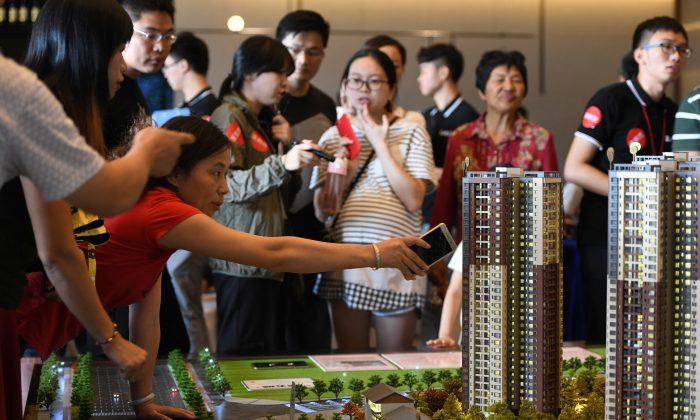 """A woman points at the model of a residential compound by China Vanke as a sales agent introduces the property to the visitors at its showroom during the National Day """"Golden Week"""" holiday, in Dongguan, Guangdong Province, China on Oct. 2, 2018. (Reuters)"""