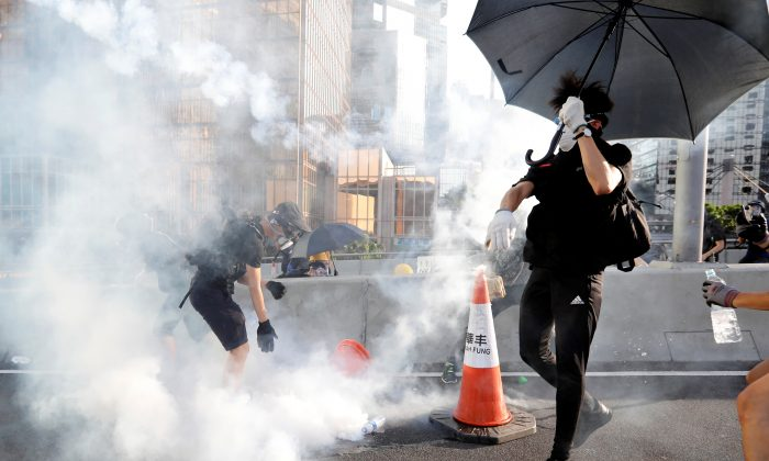 Protesters react after tear gas was fired by the police during a demonstration in support of the city-wide strike and to call for democratic reforms outside Central Government Complex in Hong Kong, China, Aug. 5, 2019. (Reuters/Kim Kyung-Hoon)